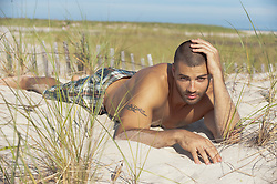 sexy man with a tattoo on the beach