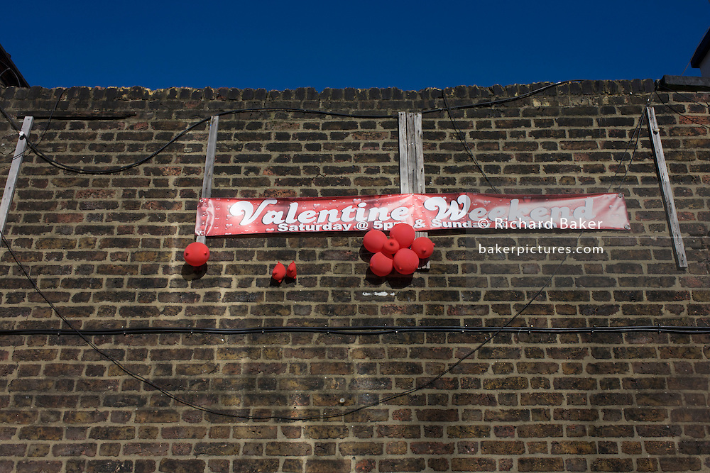 Deflated red love balloons and a Valentines Weekend banner on a brick wall in south London.