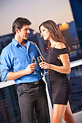 Romantic Couple Enjoying Happy Hour On A Balcony At Dusk