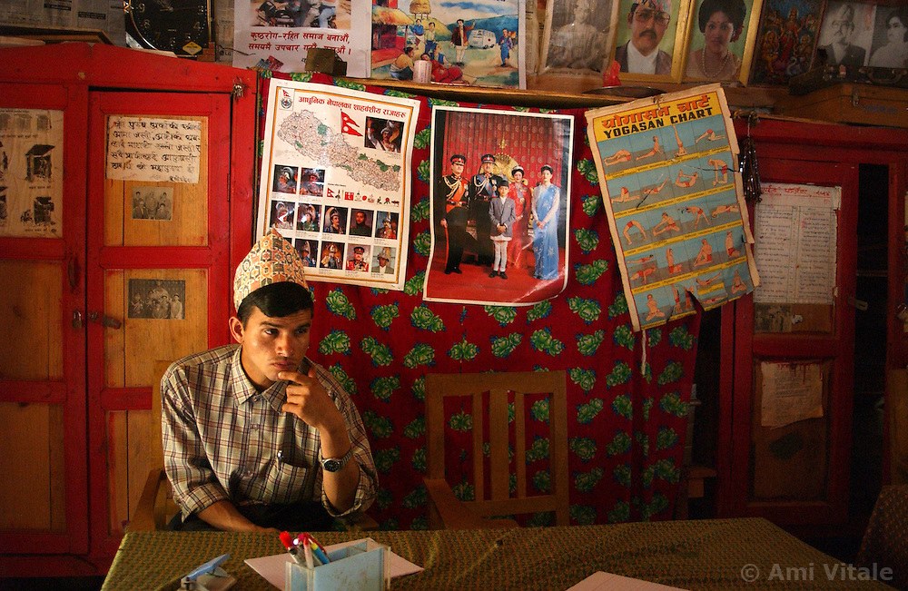 """RUKUM DISTRICT, NEPAL, APRIL 16, 2004:  A Maoist teacher sits in a government school underneath posters of the Royal Nepalese family in Rukum District April 16, 2004. The Maoists inten to close the government schools and establish their own educational system. Analysts and diplomats estimate there about 15,000-20,000 hard-core Maoist fighters, including many women, backed by 50,000 """"militia"""".  In their remote strongholds, they collect taxes and have set up civil administrations, and people's courts. They also raise money by taxing villagers and foreign trekkers.  They are tough in Nepal's rugged terrain, full of thick forests and deep ravines and the 150,000 government soldiers are not enough to combat this growing movement that models itself after the Shining Path of Peru. (Ami Vitale/Getty Images)"""