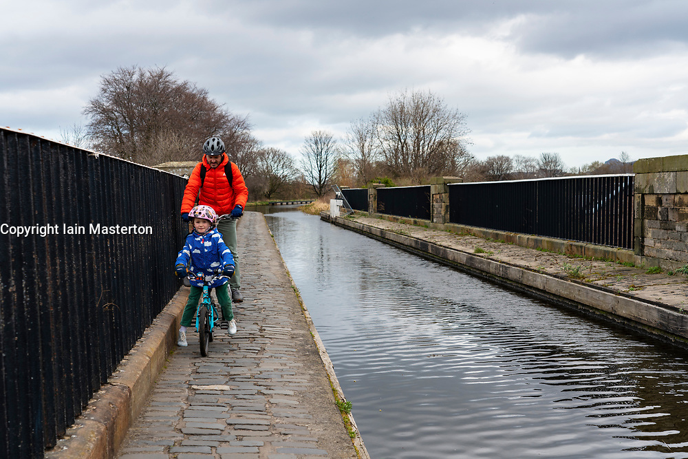 Cyclists crossing aqueduct carrying the Union Canal over the Water of Leith in early spring  in Edinburgh, Scotland, UK