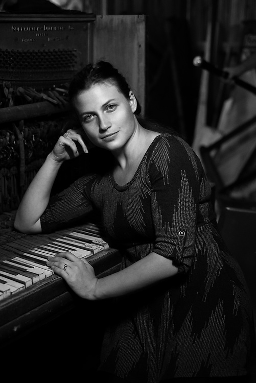 Black and white photo of a young woman by piano