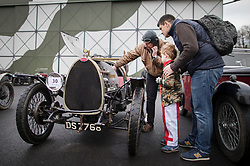 © Licensed to London News Pictures. 28/01/2018. Weybridge, UK. Driver Ed Burgess shows the engine of his 1924 Bugatti T13 Brescia to Thomas Morley (5) and his dad at Brooklands Museum after taking part in The Vintage Sports-Car Club's New Year driving tests round the historic motor racing circuit. Photo credit: Peter Macdiarmid/LNP