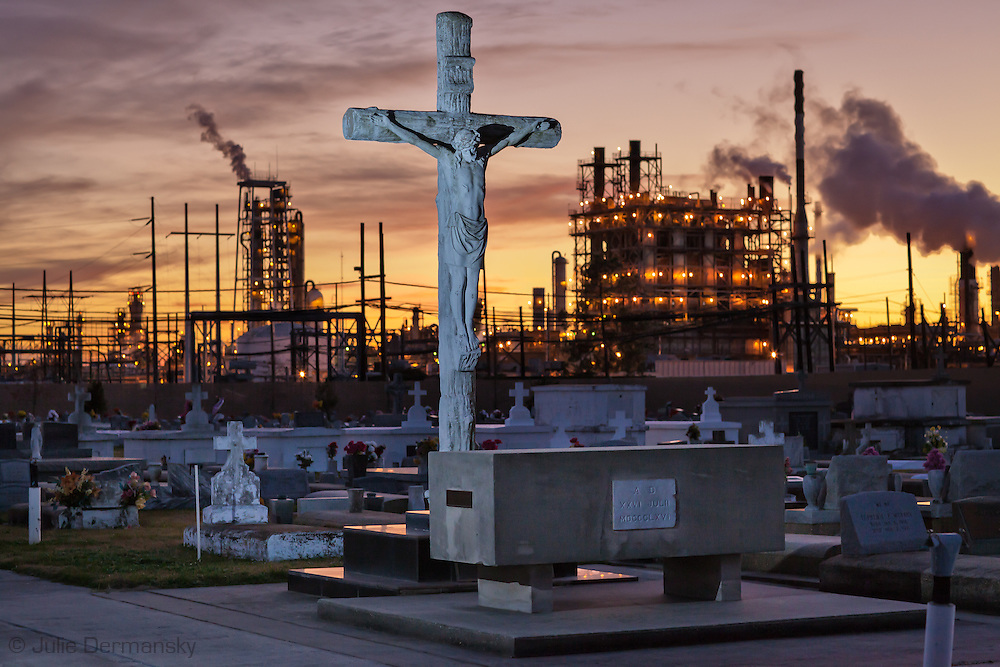 """The Holy Rosary Cemetery next to Dow Chemical (formally Union Carbide Complex) in Taft Louisiana is located  across from  the Mississippi River in the stretch between Baton Rouge and New Orleans,  is part of a large concentration of chemical and oil companies that was formerly referred to as the """"Petrochemical Corridor,"""" but now is know as """"Cancer Alley.""""  Many cases of cancer have occurred  in communities on both sides of the river though the Louisiana Tumor Registry claims the numbers are not higher then the national average. The record high levels of the Mississippi River in the spring of 2011 brought on by what some scientists classify as climate change,  threaten the environment with the potential flooding of industrial complexes and nuclear facilities along the river."""