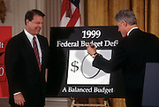 US President Bill Clinton draws a giant zero on a sign as he and Vice President Al Gore unveil the first balanced federal budget in the East Room of the White House February 2, 1999 in Washington, DC.