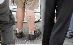 © Licensed to London News Pictures. 19/08/2012. A tattoo on the leg of a supporter of Julian Assange waiting for  Wikileaks founder Julian Assange speaking from a balcony at The Ecuador Embassy in London on August 19/08/2012. Assange, who faces arrest by British police if he leaves the building, took refuge in the embassy on June 19 to evade extradition to Sweden where he is wanted for questioning over alleged sexual misconduct. Photo credit : Ben Cawthra/LNP