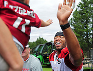 Jul. 28, 2012; Flagstaff, AZ, USA; Arizona Cardinals wide receiver Larry Fitzgerald (11) gives a high five to a fan prior to practice at training camp on the campus of Northern Arizona University.  Mandatory Credit: Jennifer Stewart-US PRESSWIRE.