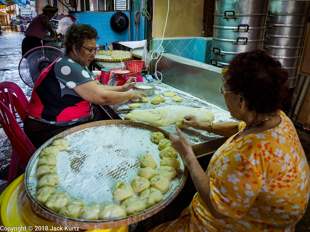 "12 FEBRUARY 2018 - BANGKOK, THAILAND: Women prepare steamed buns in a home that makes steamed Chinese buns, called ""bao"" in the Chinatown neighborhood of Bangkok. Bao are eaten at midnight on the Lunar New Year and served to guests during New Year's entertaining. Lunar New Year, also called Tet or Chinese New Year, is 16 February this year. The coming year will be the Year of the Dog. Thailand has a large Chinese community and Lunar New Year is widely celebrated in Thailand, especially in Bangkok and large cities with significant Chinese communities.    PHOTO BY JACK KURTZ"