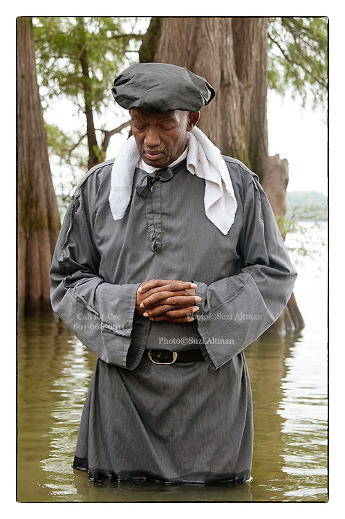 Traditional African american baptisms at Moon Lake Mississippi. <br /> A 100 yr. Tradition of rural African American Baptisms on Moon Lake, in the Mississippi Delta held once a year in the same spot on the lake. The First candidate for baptism is pictured in the water before he is Baptised. (photo© Suzi Altman)