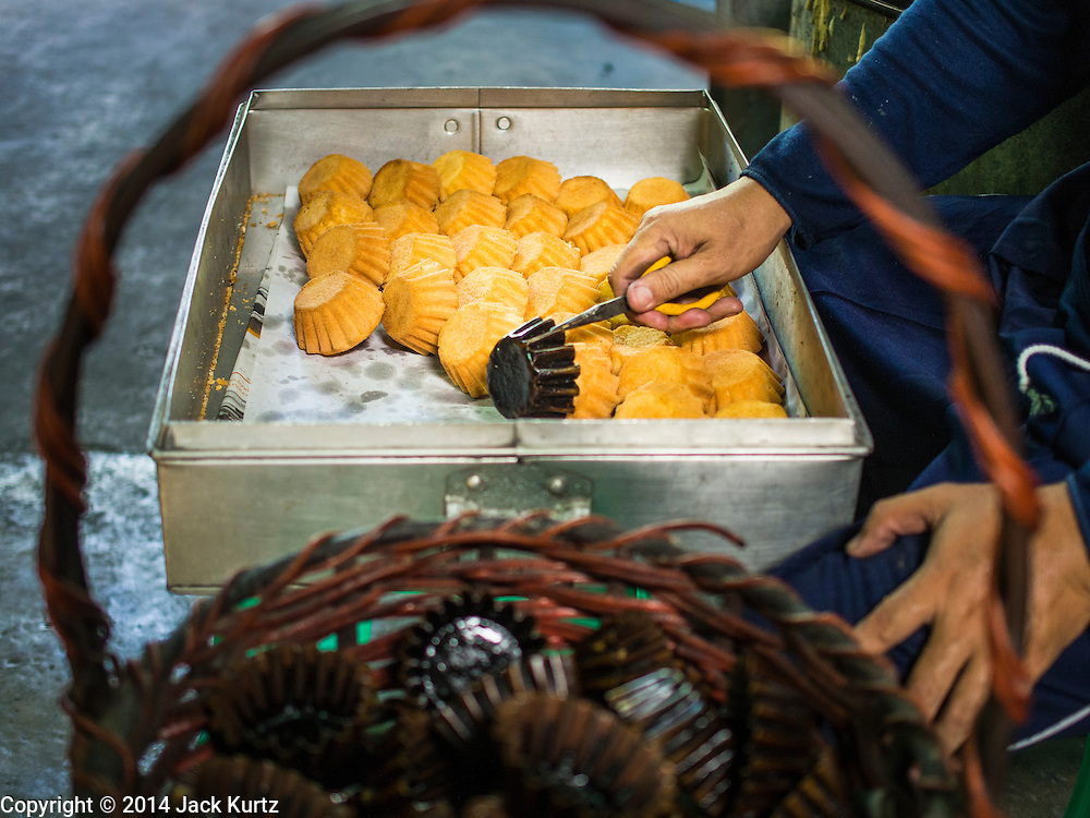 """28 OCTOBER 2014 - BANGKOK, THAILAND: A worker pulls cakes out of the oven at the Pajonglak Maneeprasit Bakery in Bangkok. The cakes are called """"Kanom Farang Kudeejeen"""" or """"Chinese Monk Candy."""" The tradition of baking the cakes, about the size of a cupcake or muffin, started in Siam (now Thailand) in the 17th century AD when Portuguese Catholic priests accompanied Portuguese soldiers who assisted the Siamese in their wars with Burma. Several hundred Siamese (Thai) Buddhists converted to Catholicism and started baking the cakes. When the Siamese Empire in Ayutthaya was sacked by the Burmese the Portuguese and Thai Catholics fled to Thonburi, in what is now Bangkok. The Portuguese established a Catholic church near the new Siamese capital. Now just three families bake the cakes, using a recipe that is 400 years old and contains eggs, wheat flour, sugar, water and raisins. The same family has been baking the cakes at the Pajonglak Maneeprasit Bakery, near Santa Cruz Church, for more than 245 years. There are still a large number of Thai Catholics living in the neighborhood around the church.   PHOTO BY JACK KURTZ"""