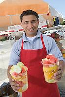 Portrait of male street vendor holding fruit salad