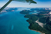 """Aerial view of West Arm of <br /> Glacier Bay National Park, Alaska, USA. Flightseeing from Skagway or Haines is a spectacular way to see Glacier Bay. We were bedazzled by Mountain Flying Service's 1.3-hour West Arm tour from Skagway. Glacier Bay is honored by UNESCO as part of a huge Biosphere Reserve and World Heritage site shared between Canada and the United States. In 1750-80, Glacier Bay was totally covered by ice, which has since radically melted away. In 1794, Captain George Vancover found Icy Strait on the Gulf of Alaska choked with ice, and all but a 3-mile indentation of Glacier Bay was filled by a huge tongue of the Grand Pacific Glacier, 4000 feet deep and 20 miles wide. By 1879, naturalist John Muir reported that the ice had retreated 48 miles up the bay. In 1890, """"Glacier Bay"""" was named by Captain Beardslee of the U.S. Navy. Over the last 200 years, melting glaciers have exposed 65 miles of ocean. As of 2019, glaciers cover only 27% of the Park area. Since the mid 1900s, Alaska has warmed 3 degrees Fahrenheit and its winters have warmed nearly 6 degrees. Human-caused climate change induced by emissions of greenhouse gases continues to accelerate warming at an unprecedented rate. Climate change is having disproportionate effects in the Arctic, which is heating up twice as fast as the rest of Earth."""