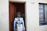A woman stands by her front door in the Langa township of Cape Town, South Africa