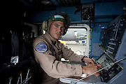 Portrait of a US Navy Sonar Operator who interprets acoustic warfare equipment doppler signals on a Sikorsky MH-60R helicopter at the Farnborough Airshow. The MH-60R is the U.S. Navy's newest and most advanced multi-mission helicopter, designed for anti-submarine and surface warfare (ASW/ASuW). Secondary missions include: Search and Rescue, anti-ship surveillance and targeting, communication relay and medevac/vertical replenishment. The Sikorsky-built helicopter with integrated avionics and mission systems by Lockheed Martin.