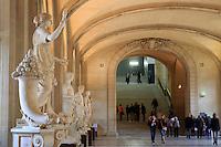 Visitors enjoy the Ancient Roman sculptures in The Louvre Museum, Paris, France.