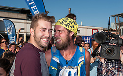 © Licensed to London News Pictures. 05/10/2016. Bristol, UK. Marathon runner BEN SMITH with his partner Kyle at the finish of his final 401st marathon, in Millennium Square in Bristol harbour side. Ben has been undertaking a 'World Record' attempt which will see him have run 401 marathons in 401 consecutive days around 309 different locations of the UK mainland. The challenge aims to raise both awareness of the issues of bullying in society along with £250,000 for two charities dedicated to tackling bullying, 'Stonewall' and 'Kidscape'. Both these charities work to support award winning initiatives which against bullying in UK schools and society in all its forms. Ben came out as a gay man at the age of 31. Photo credit : Simon Chapman/LNP