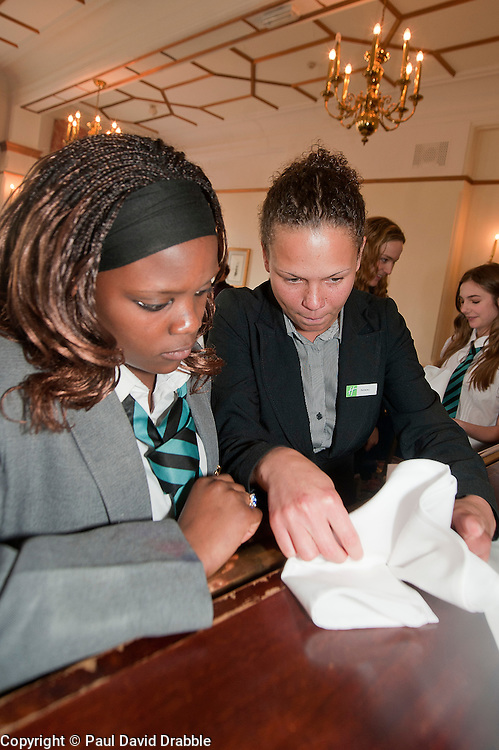 """Hospitality Sheffield's """"Spring Forward"""" initiative aimed at attracting the next generation of hospitality professionals took place in Sheffield on Thursday 8th March..Nikki Lucas Holiday Inn Royla Victoria Food Services Manager teaches Lindi Dube of Parkwood Academy how to correctly fold a napkin into a fan tail for a restaurant table...http://www.pauldaviddrabble.co.uk..3  March 2012 -  Image © Paul David Drabble"""