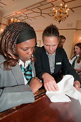 "Hospitality Sheffield's ""Spring Forward"" initiative aimed at attracting the next generation of hospitality professionals took place in Sheffield on Thursday 8th March..Nikki Lucas Holiday Inn Royla Victoria Food Services Manager teaches Lindi Dube of Parkwood Academy how to correctly fold a napkin into a fan tail for a restaurant table...http://www.pauldaviddrabble.co.uk..3  March 2012 -  Image © Paul David Drabble"
