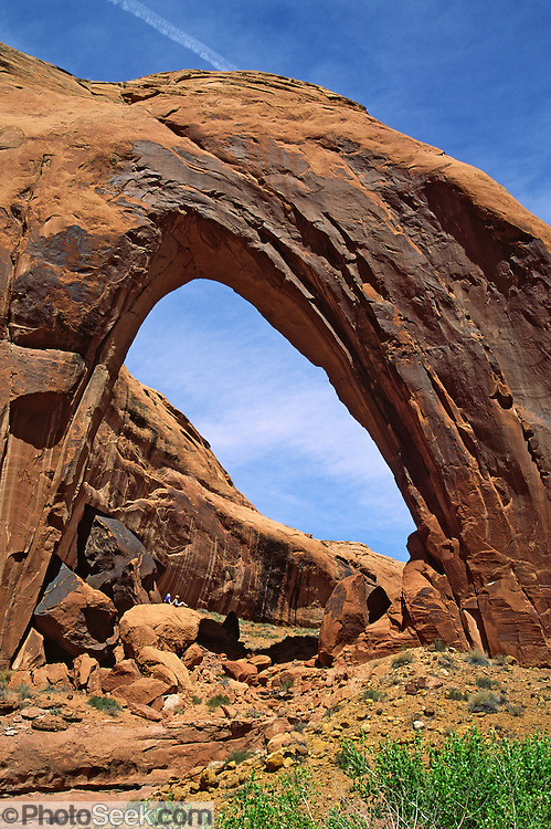 Tiny hikers sit beneath massive Broken Bow Arch, in Glen Canyon National Recreation Area, Utah, USA.