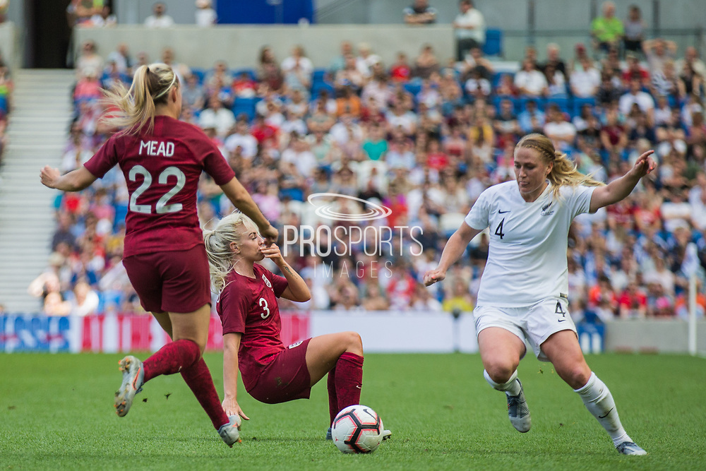 Beth Mead (England) & CJ Bott (New Zealand) with Alex Greenwood (England) falling to the ground in the background during the FIFA Women's World Cup UEFA warm up match between England Women and New Zealand Women at the American Express Community Stadium, Brighton and Hove, England on 1 June 2019.