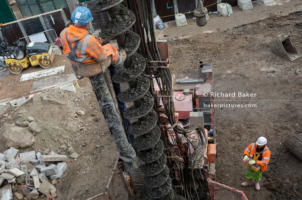 Watched by a colleague on the ground who controls the machinery, a workman kicks off sticking materials from a soil drill, on 6th November 2019, at Wembley Stadium, London, England.