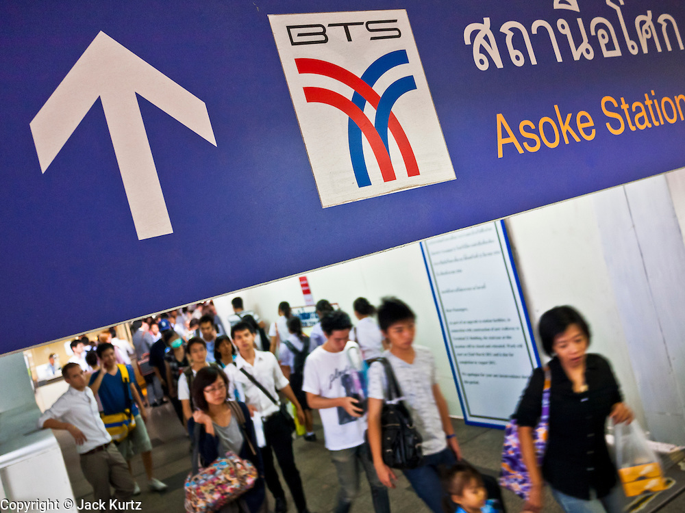14 JULY 2011 - BANGKOK, THAILAND:   People leave the Asoke station on the Sukhumvit line of the BTS Skytrain in Bangkok. The Bangkok Mass Transit System, commonly known as the BTS Skytrain, is an elevated rapid transit system in Bangkok, Thailand. It is operated by Bangkok Mass Transit System Public Company Limited (BTSC) under a concession granted by the Bangkok Metropolitan Administration (BMA). The system consists of twenty-three stations along two lines: the Sukhumvit line running northwards and eastwards, terminating at Mo Chit and On Nut respectively, and the Silom line which plies Silom and Sathon Roads, the Central Business District of Bangkok, terminating at the National Stadium and Wongwian Yai. The lines interchange at Siam Station and have a combined route distance of 55 km.    PHOTO BY JACK KURTZ