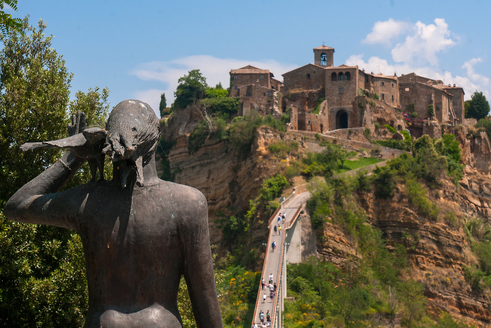 A view of the village of Civita di Bagnoregio and of the statue before reaching the bridge to the town.<br /> Civita di Bagnoregio is a town in the Province of Viterbo in central Italy, a suburb of the comune of Bagnoregio, 1 kilometre (0.6 mi) east from it. It is about 120 kilometres (75 mi) north of Rome. Civita was founded by Etruscans more than 2,500 years ago. Bagnoregio continues as a small but prosperous town, while Civita became known in Italian as La citt&agrave; che muore (&quot;The Dying Town&quot;). Civita has only recently been experiencing a tourist revival. The population today varies from about 7 people in winter to more than 100 in summer.The town was placed on the World Monuments Fund's 2006 Watch List of the 100 Most Endangered Sites, because of threats it faces from erosion and unregulated tourism.