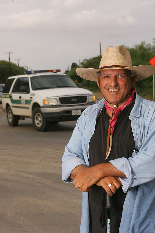 Jay Johnson Castro poses for a portrait at the end of his 15th day of walking as a US Border Patrol vehicle passes by.