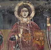Fresco of a saint holding a box and an instrument in the nave of the Dormition of Saint Mary Cathedral Church, or Kisha Katedrale Fjetja e Shen Marise, built 1699, Voskopoje, Korce, Albania. The church contains frescoes by Theodor Anagnost and Sterian from Agrapha in Greece, and the large icons in the iconostasis were painted 1703 by Constantine Lemoronachos. Picture by Manuel Cohen