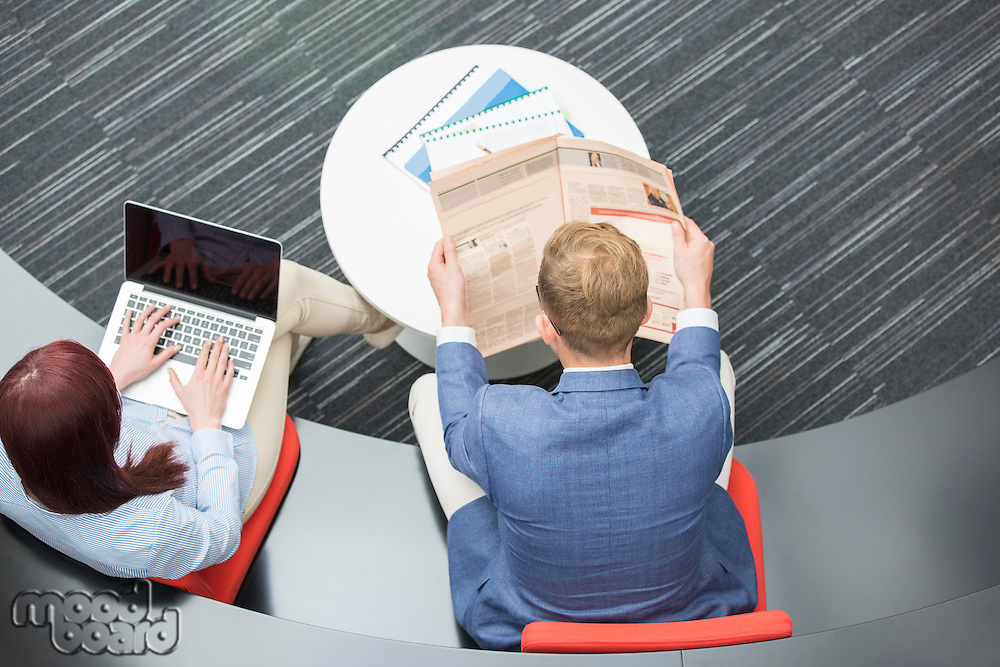 High angle view of businessman reading newspaper while female colleague using laptop in office