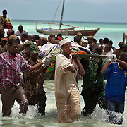 Dead bodies are carried to shore after a tragic ferry accident off the coast of Zanzibar.