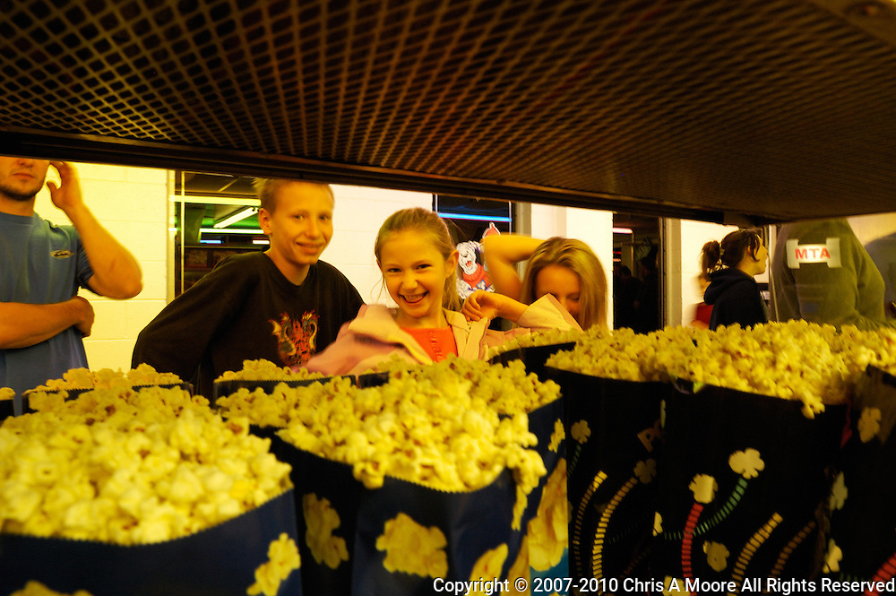 The two girls on the other side of the popcorn warmer spot the camera and start vamping fro the photographer.  The boy is smiling but isn't as demonstrative as the girls.