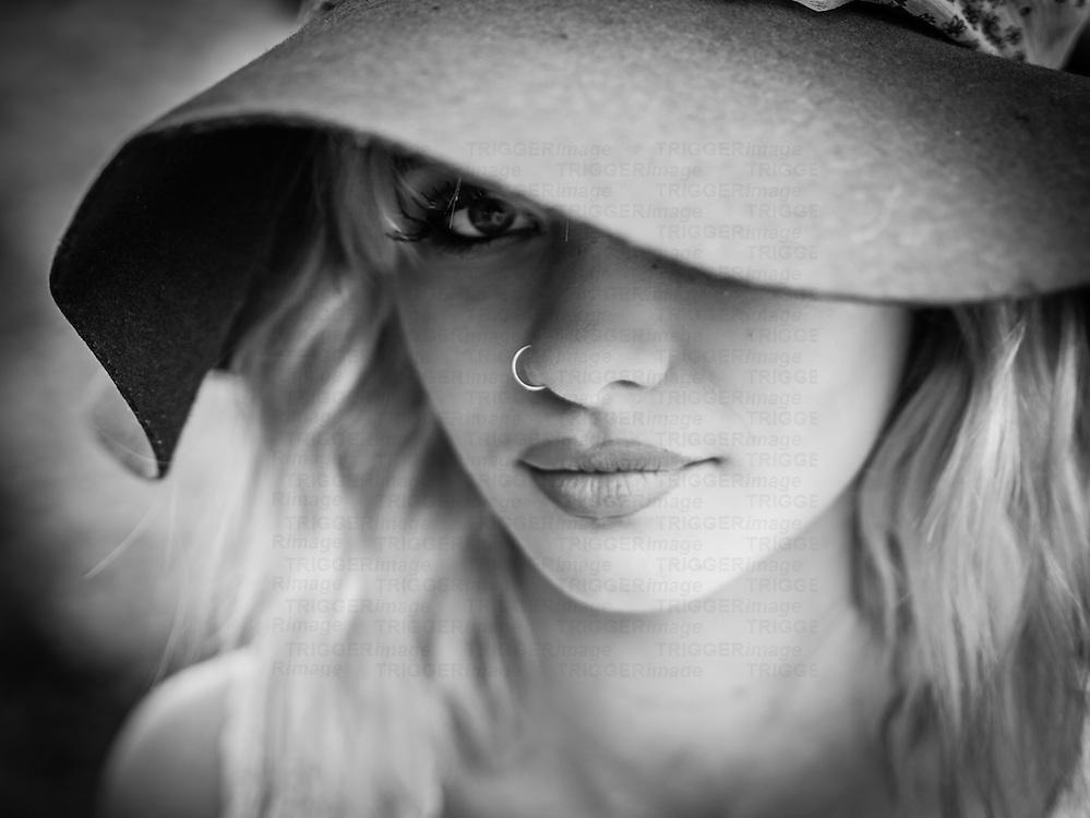 Closeup shot of a young female model in a hat.