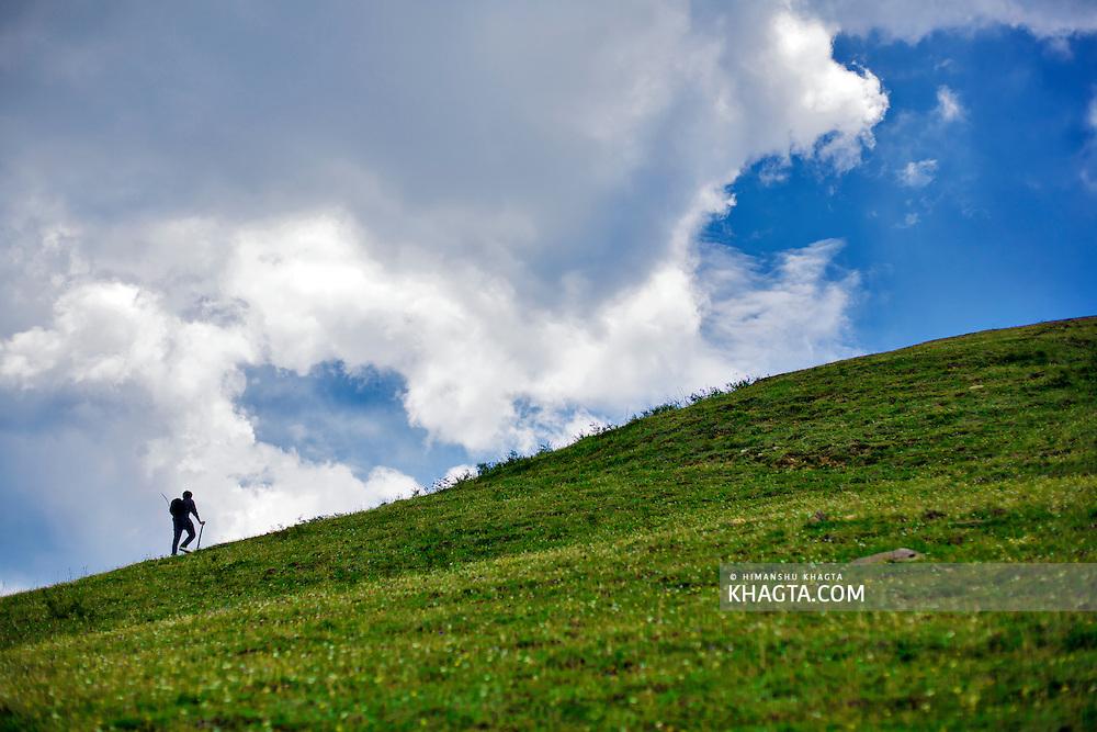 A trekker climbing the meadows of Kuppar, few kilometers from Shimla.