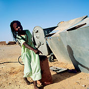 A Saharawi refugee girl brings water to her tent at the refugee camp of Awserd, Tindouf (Algeria). Drinking water is brought to the refugee camps by lorries from Tindouf. The water is loaded in tanks in each of the four wilayas (districts) for their distribution to the Saharawi families