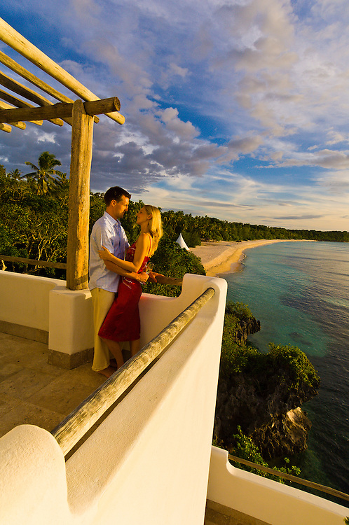 A couple on honeymoon enjoy the sunset from The Point, a villa above Vatulele Island Resort, Fiji Islands