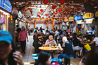 A busy hawker center with a variety of food stalls in downtown Singapore.