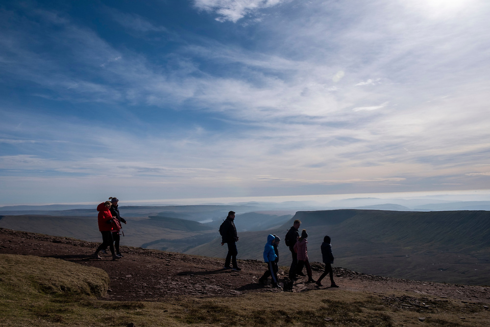 A group of adults and children walk along a dirt path descending from the summit of Pen Y Fan mountain in Brecon Beacons National Park, Wales, Powys, United Kingdom.  Pen Y Fan is the highest point in the Brecon Beacons hill and mountain range in South Wales. The National Park was established in 1957 due to the spectacular landscape which is rich in natural beauty and is run by the National Trust.  (photo by Andrew Aitchison / In pictures via Getty Images)