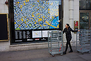 Woman walks two retail merchandise cages near a street map of London's West End.