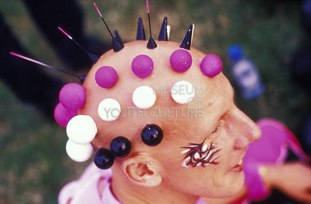 Skin head man with painted balls stuck to his head, cyber gear, Creamfields, UK, 2000