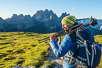 A close-up view of a male photographer as seen on a cold but sunny morning hiking and photographing on Monte Piano, South Tirol, Dolomites, Italy.