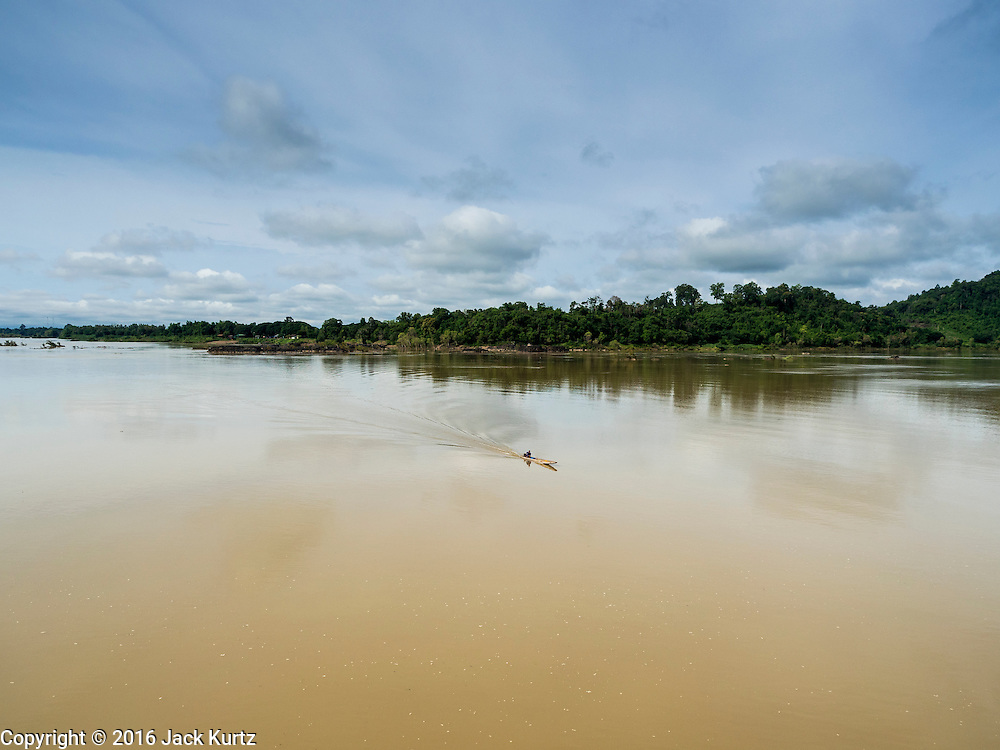 20 JUNE 2016 - DON KHONE, CHAMPASAK, LAOS: A man in motorized canoe approaches the south end of Don Khone Island. Don Khone Island, one of the larger islands in the 4,000 Islands chain on the Mekong River in southern Laos. The island has become a backpacker hot spot, there are lots of guest houses and small restaurants on the north end of the island. This is the southernmost point in Laos, Cambodia is in the background.       PHOTO BY JACK KURTZ