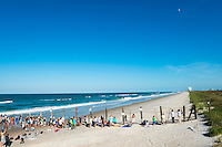 Spectators stand along a barrier separating Playalinda Beach from Cape Canaveral and the Kennedy Space Center. They are watching the launch of an Atlas V rocket, which is carrying the U.S. Air Force's fourth Block 2F navigation satellite for the Global Positioning System. The rocket is in the sky, and smoke from the blastoff remains on the launch pad.
