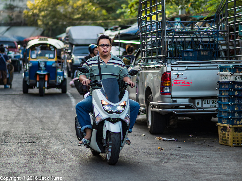 01 DECEMBER 2016 0 BANGKOK, THAILAND: A man rides her motorcycle through the traditional market on Lan Luang Road in Bangkok. The market is on the site of one of the first western style cinemas in Bangkok. The movie theatre closed years ago and is still empty but the market fills the streets around the theatre.     PHOTO BY JACK KURTZ