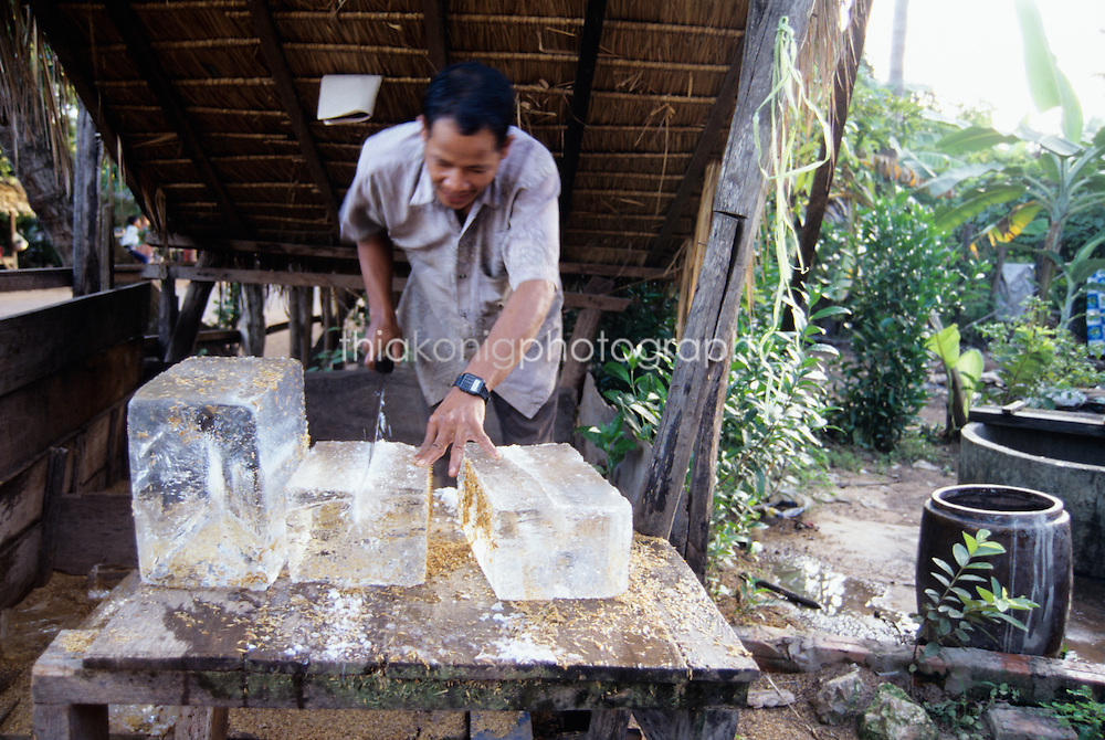 A village man cuts ice for delivery, Cambodia