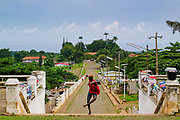 A boy dances with Roça Agostinho Neto  main street in the background. This old cocoa farm is the largest in São Tomé island.