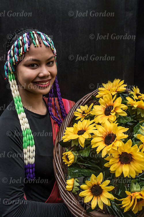 She is wearing Carnival regalia and carrying flower in basket looking into the camera showing her Paac Panag Benga ethnic pride.  She is one of the many faces in the Philippine Independence Day Parade in NYC.