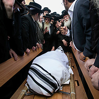 Ultra-Orthodox Jewish men gather around the body of Yeshayahu Kirshavski during his funeral in Jerusalem, Tuesday, Oct. 13, 2015. A pair of Palestinian men boarded a bus in Jerusalem and began shooting and stabbing passengers, while another terrorist rammed a car into a bus station before stabbing bystanders, in near-simultaneous attacks. <br />