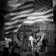 New York. People passing by an amaerican flag during the Haitian parade in Brooklyn
