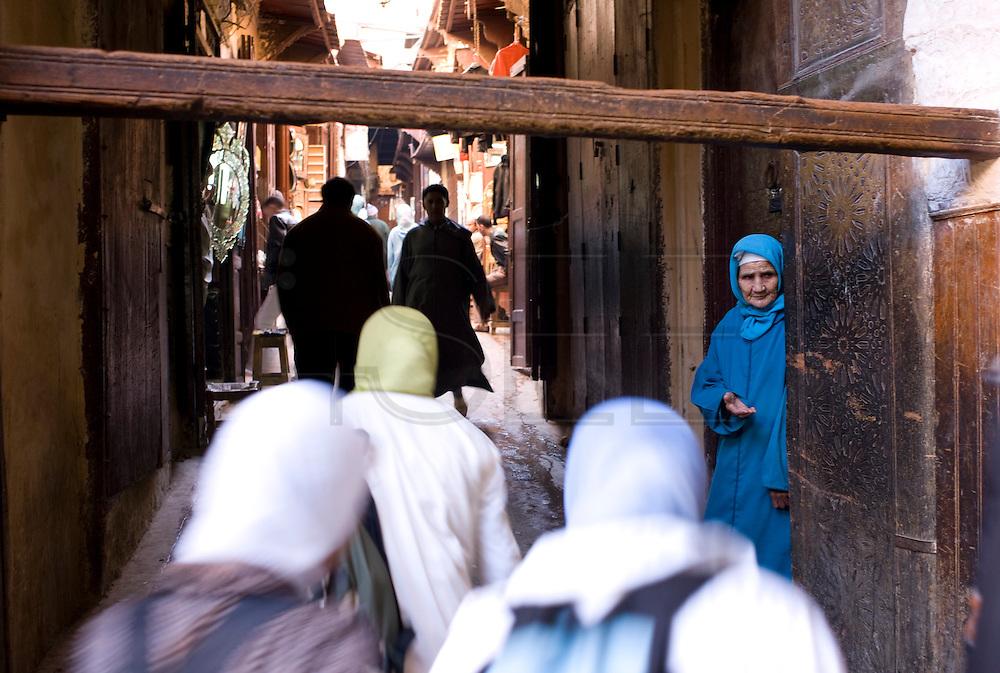 Beggar in a narrow street inside Fez Medina.